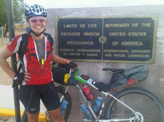A rider next to her bike with a full bikepacking bags kit showing a poster mentioning the boundary of the USA with Mexico