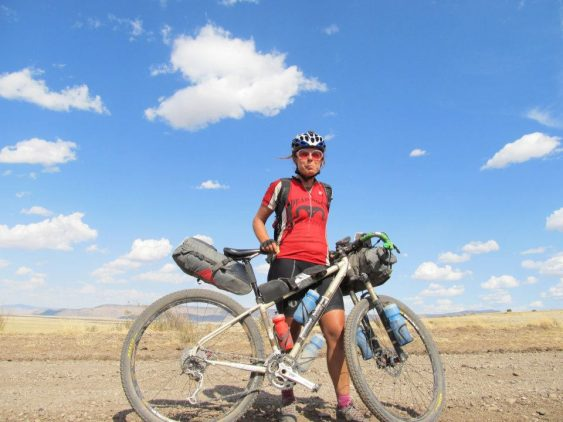 A rider next to her bike with a full bikepacking bags kit in the middle of the Tour Divide route