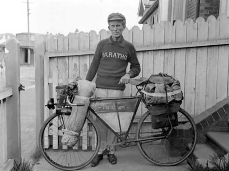 An aged man in black and white next to his bike from the 20th century with a full bikepacking bag kit from that time