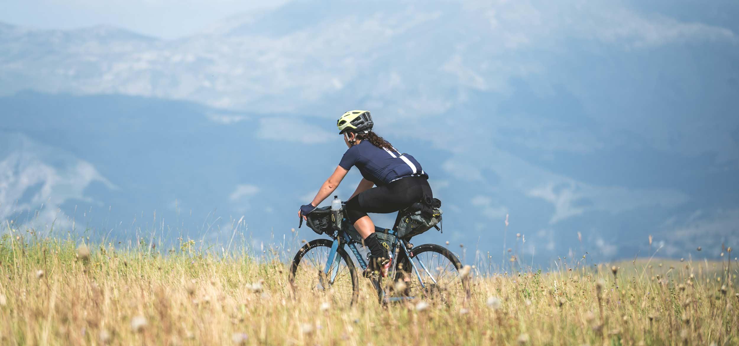 A woman bikepacking racing down a dry grass field