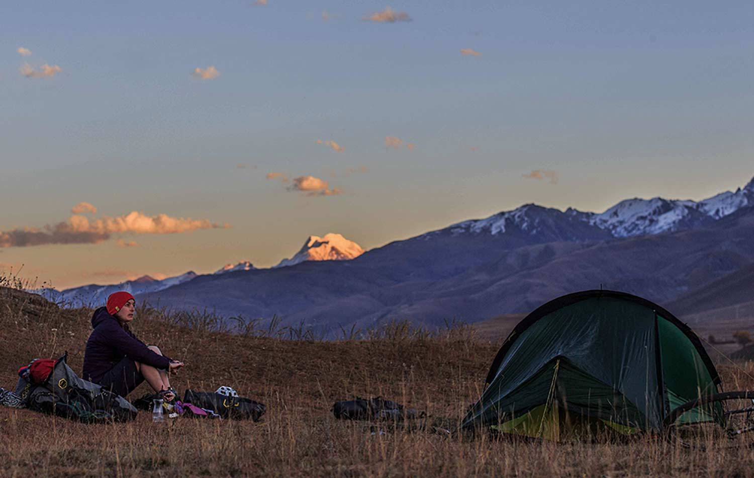 A person camping in the mountains: She is sitting outside next to the tent and their bikepacking bags