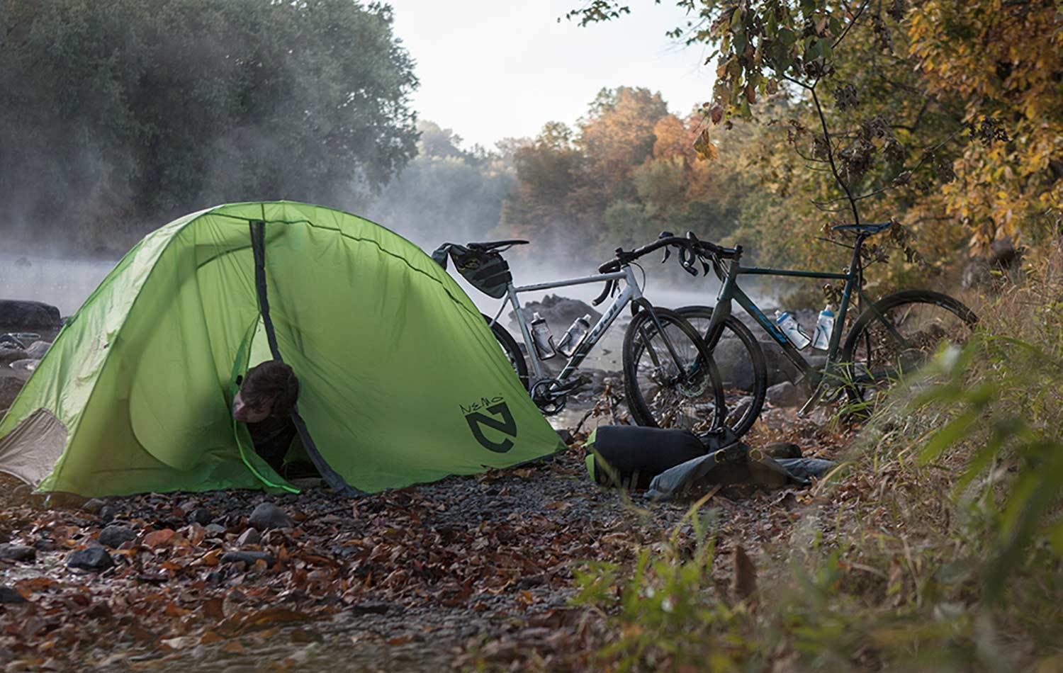 On a bank of a river, a person inside of a green tent rearing his head. Also, there are two bikes with a kit of bikepacking bags on the floor next to the camping area