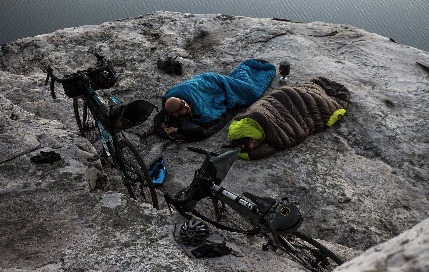 two people into sleeping bags with their bikes and bikepacking bags next to them