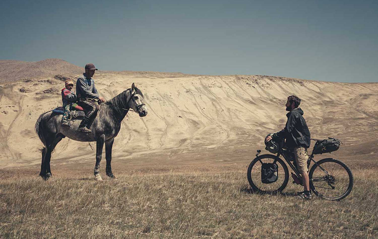 Apidura Ambassador's Marc Maurer meeting a horse rider on his journey Bikepacking in Kyrgyzstan