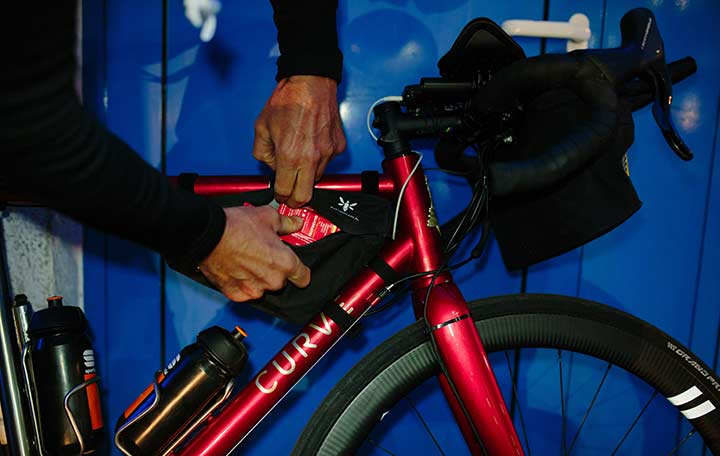 Close-up of hands opening the frame bag located in the top tube of a bike