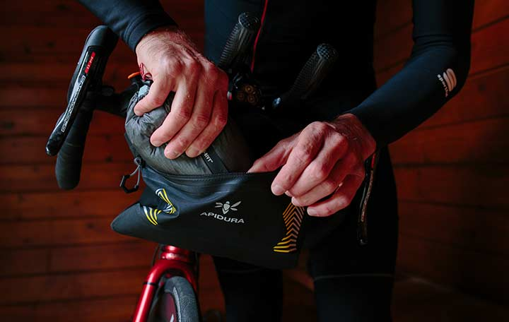 Close-up of hands putting something inside of the Saddle bag located on the seatpost of a bike