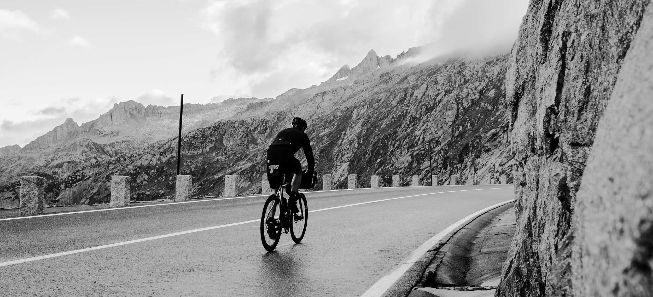 Ein Mann in einem Bikepacking-Rennen durch eine Straße, umgeben von Bergen