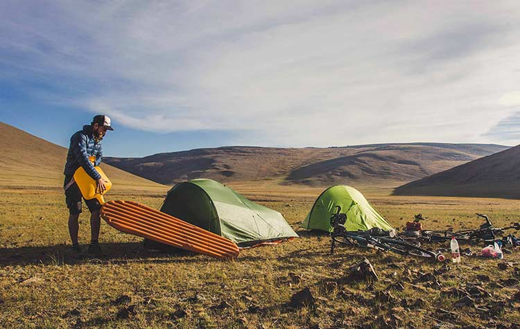 A man inflating a mattress in the middle of a desert next to two tents and a bike