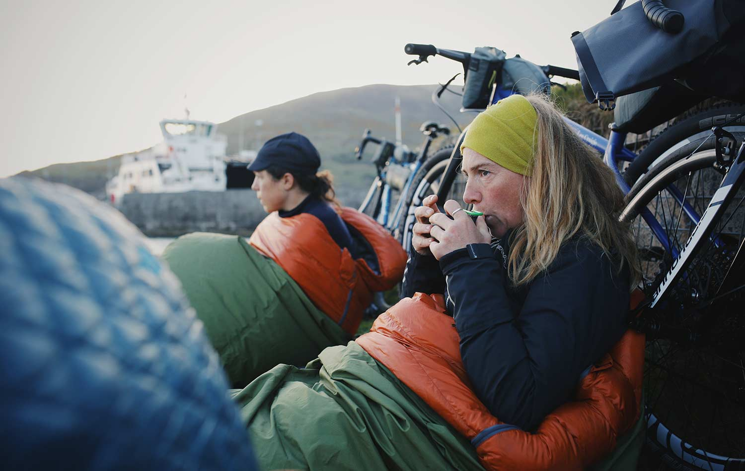 two women sitting into their sleeping bags, next to their bikes drinking a hot drink