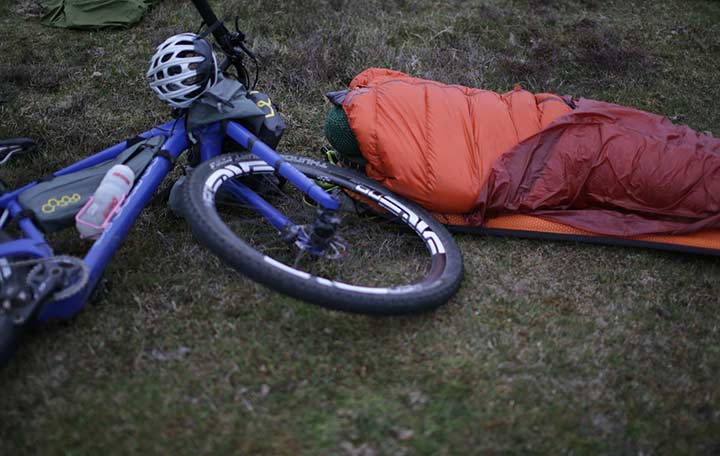 A person sleeping in the nature with a sleeping bag and a bike next to her