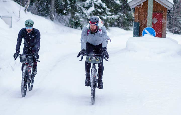 two men bikepacking in the middle of a snowing mountain