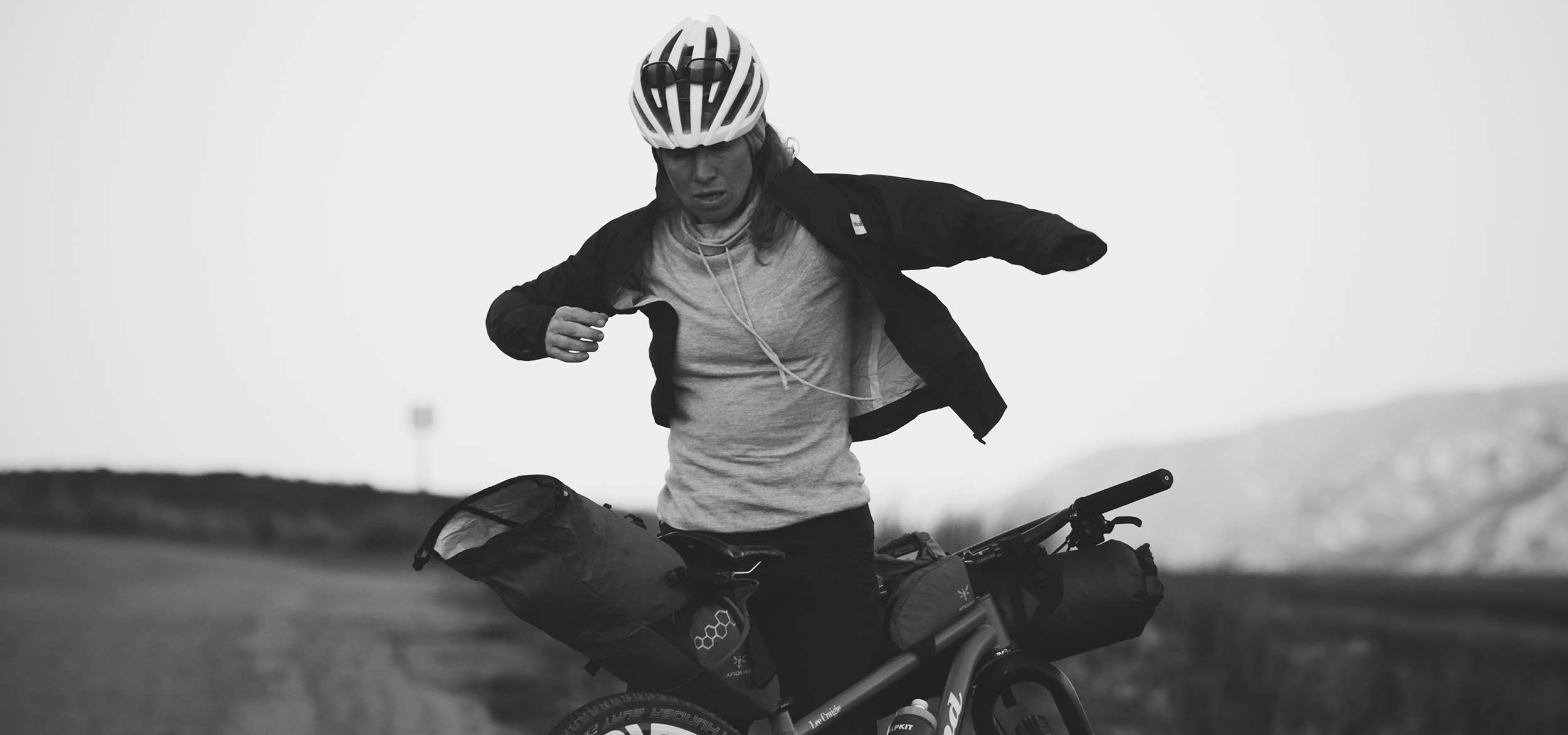 A rider beside her bicycle with a saddle and a top tube bag putting on a jacket