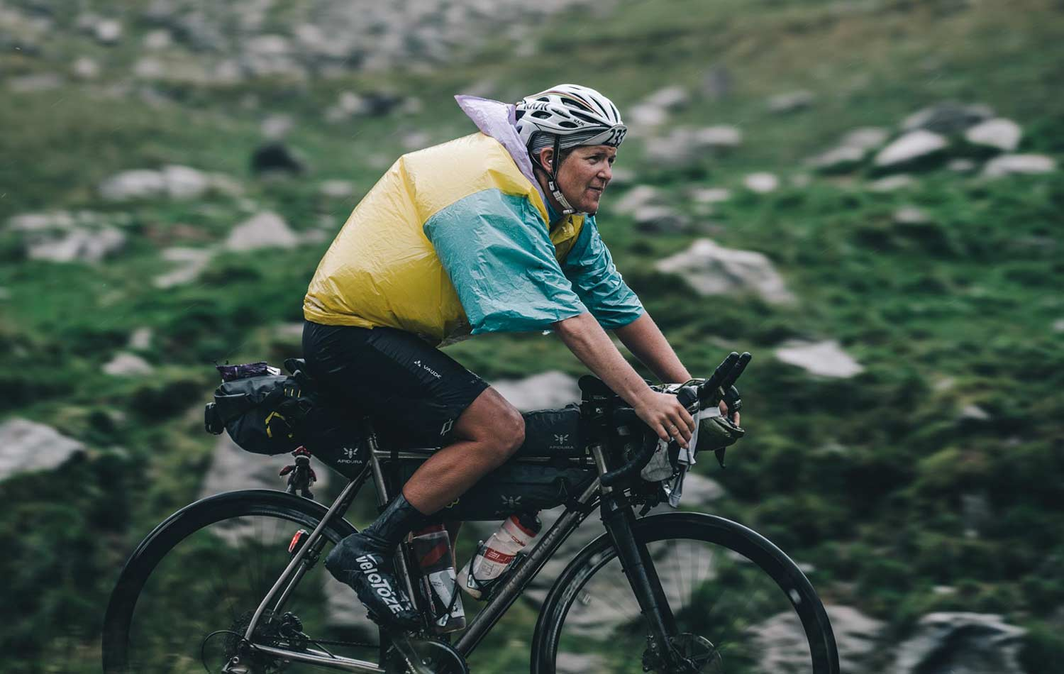 A person bikepacking with a Saddle and frame bag, wearing a disposable ponchos