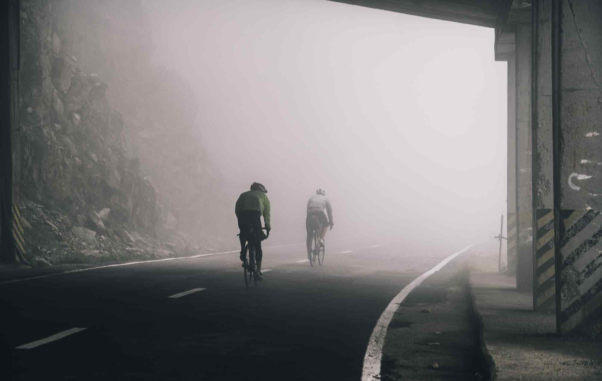 two cyclist in a foggy road