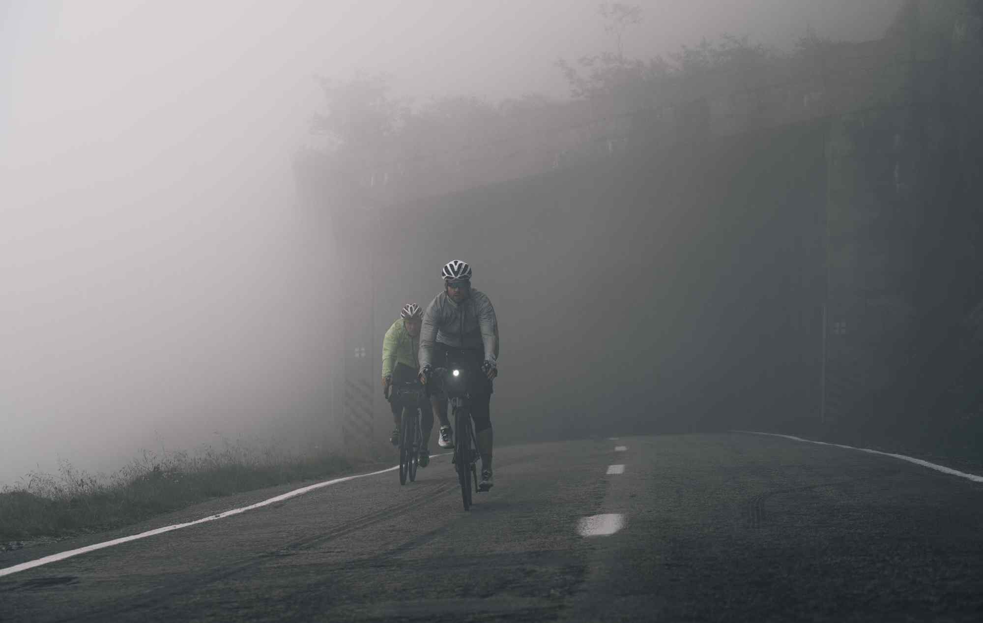 Two me riding their bikes in a foggy road