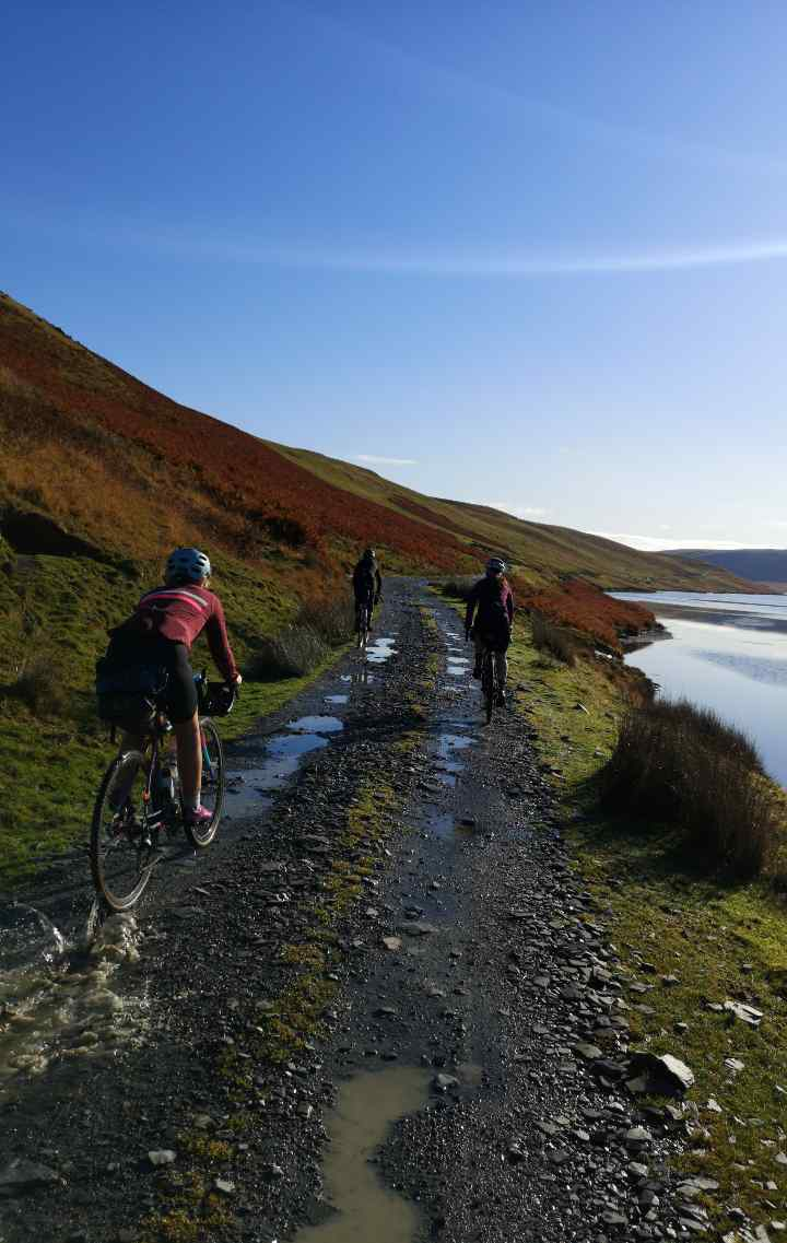 three people riding their bikes on the Gravel reservoir road