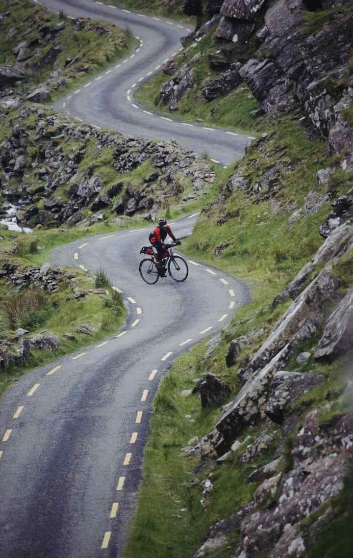 A person riding a bike in a road into the mountains
