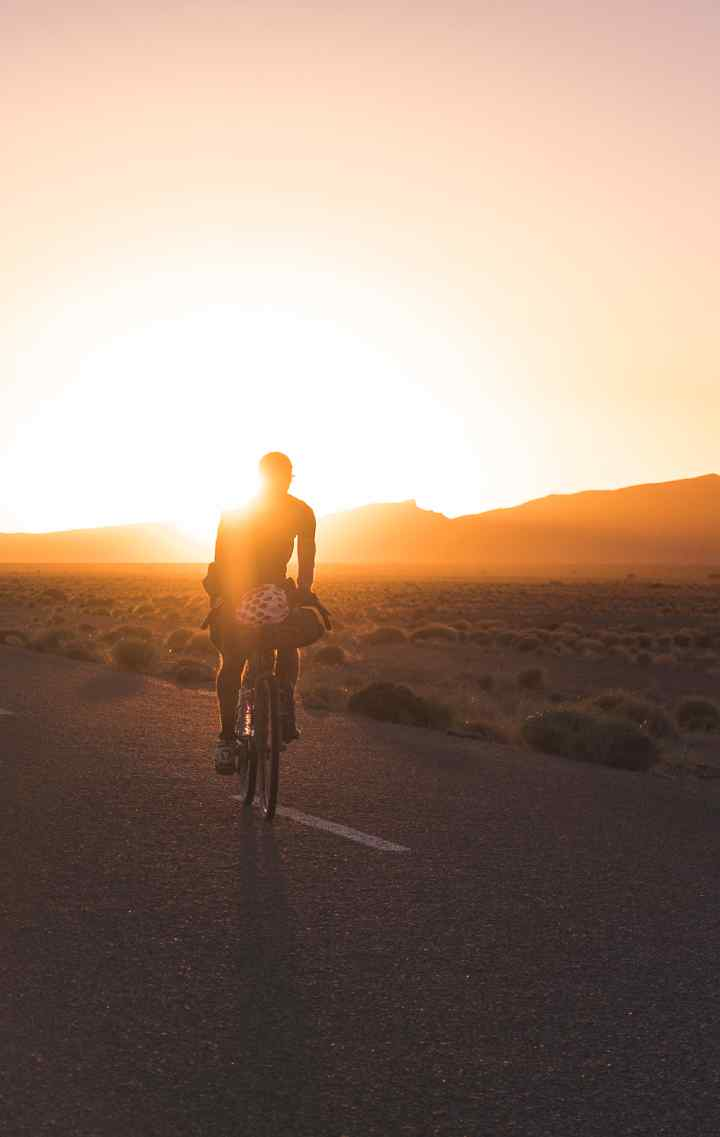 A man cycling during sunset in a desert road