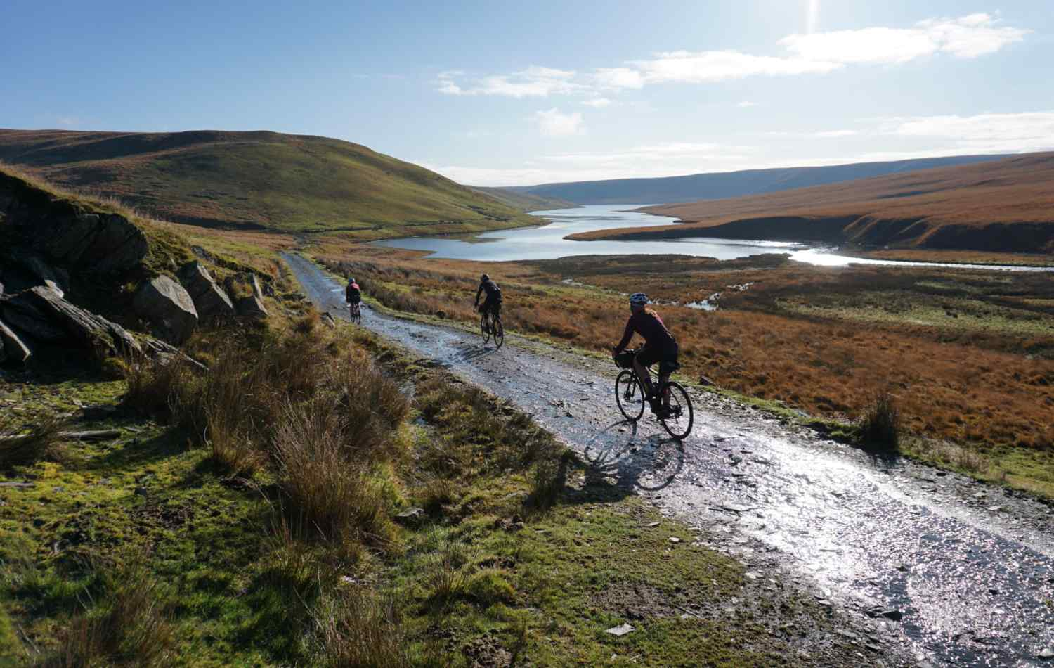 three people cycling on a Gravel Road in Wales