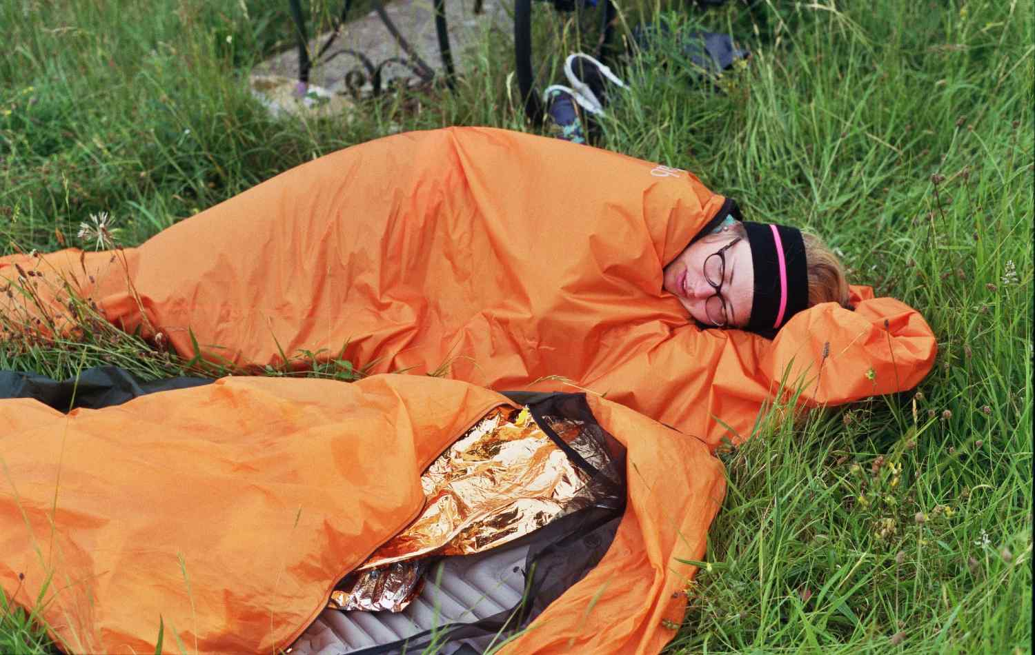 A woman sleeping into an orange sleeping bag