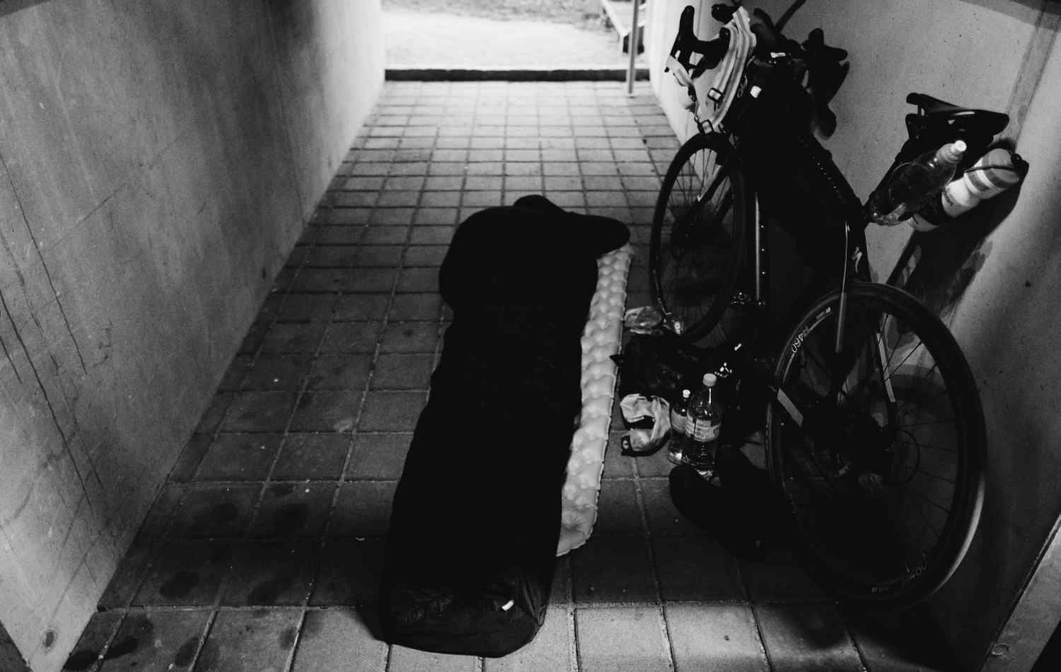A cyclist into a sleeping bag in the floor next to his bike with a full bikepacking gear
