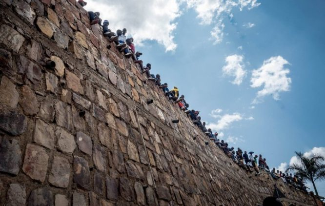 people sitting at the top of a wall