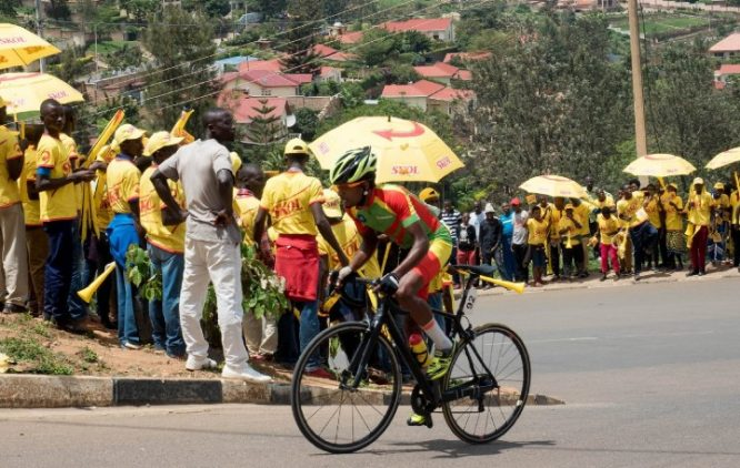 People on the streets wearing yellow t shirts waiting for the riders