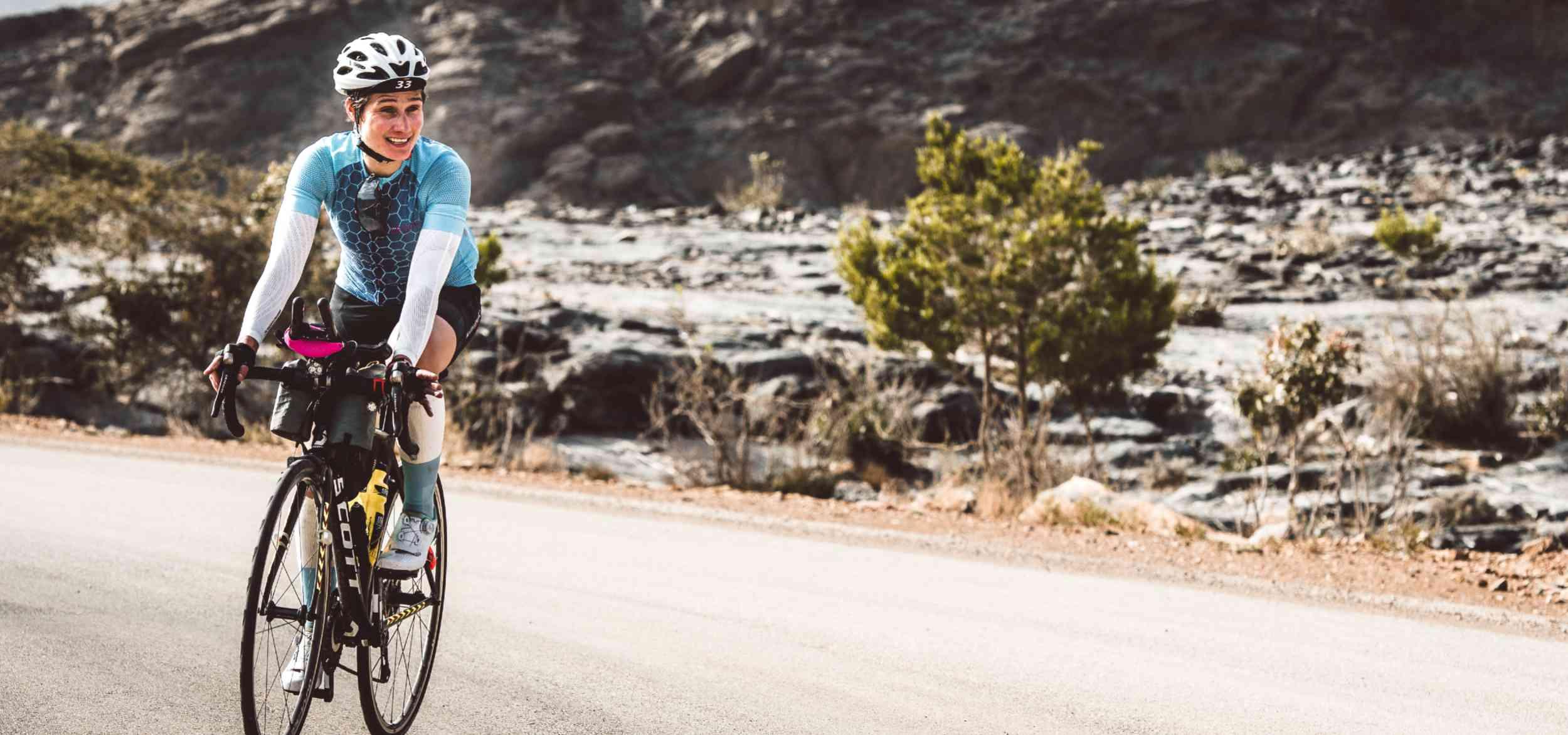 A woman riding a bike down a road