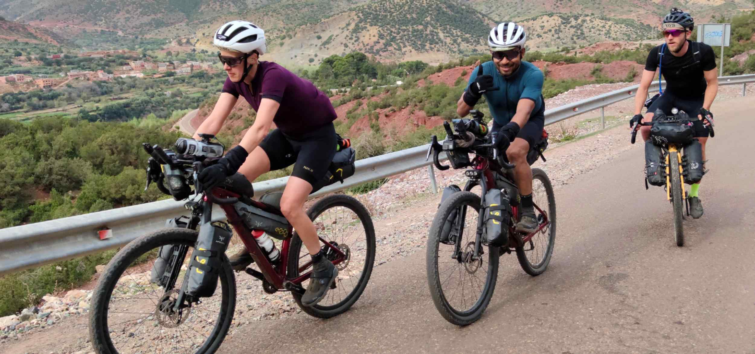 Three bikepackers riding their bikes on the road in the mountains