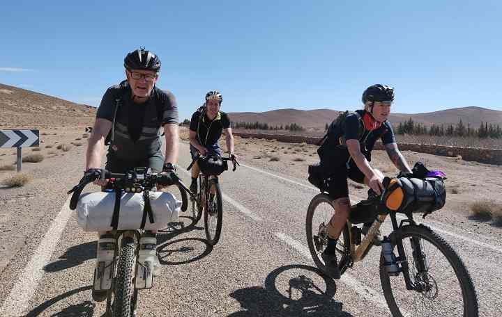 Three cyclists riding their bike with a full bikepacking gear