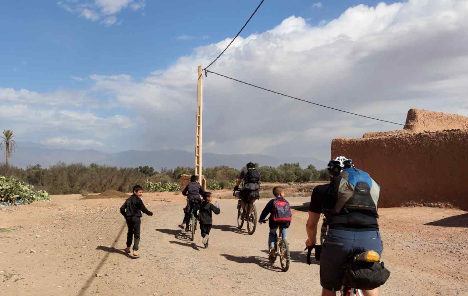 Two adults and two children riding their bikes in a Moroccan Village
