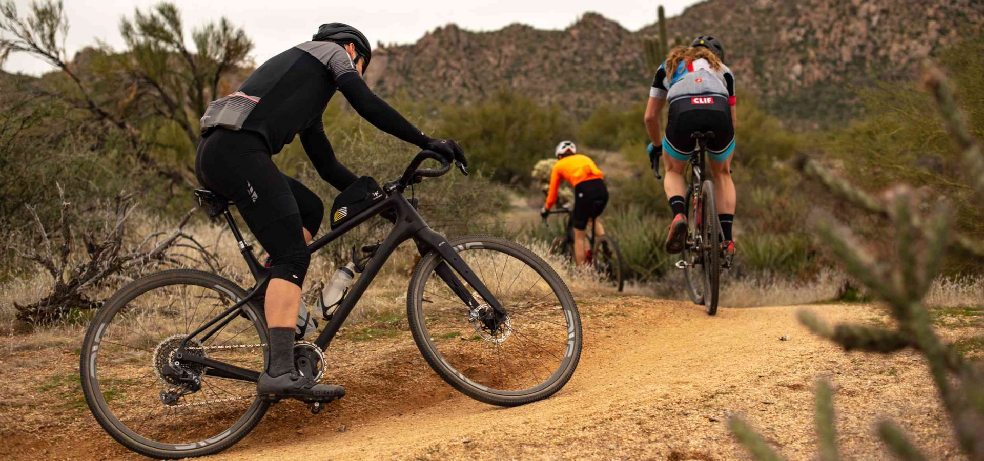 three people cycling in a mountain with their gravel bikes and a top tube bag