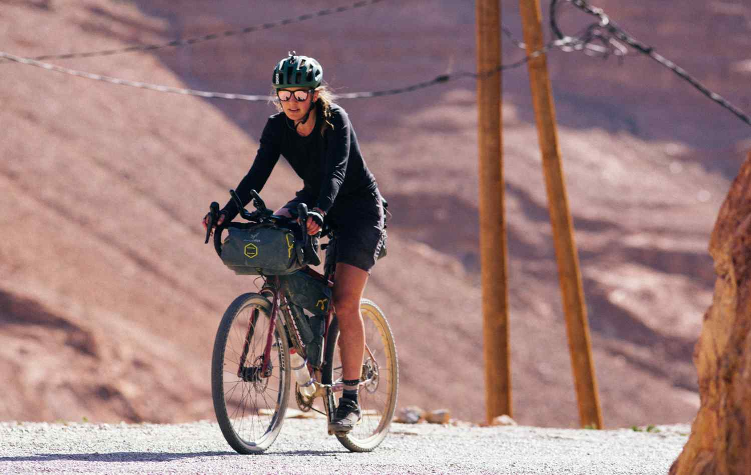 A woman riding a bike with a saddle bag and a frame bag on it