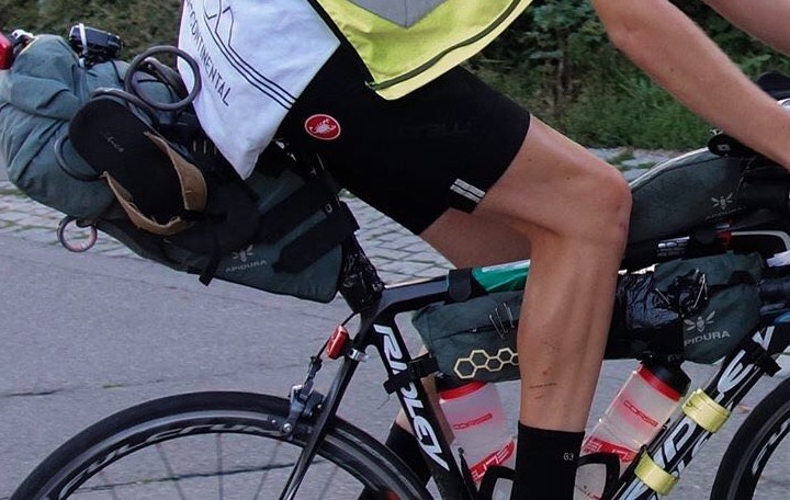 A closeup of the waist down of a person riding a bike focused on a saddle bag and a frame bag