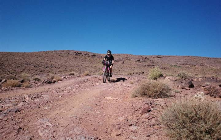 A woman riding a bike in the mountain