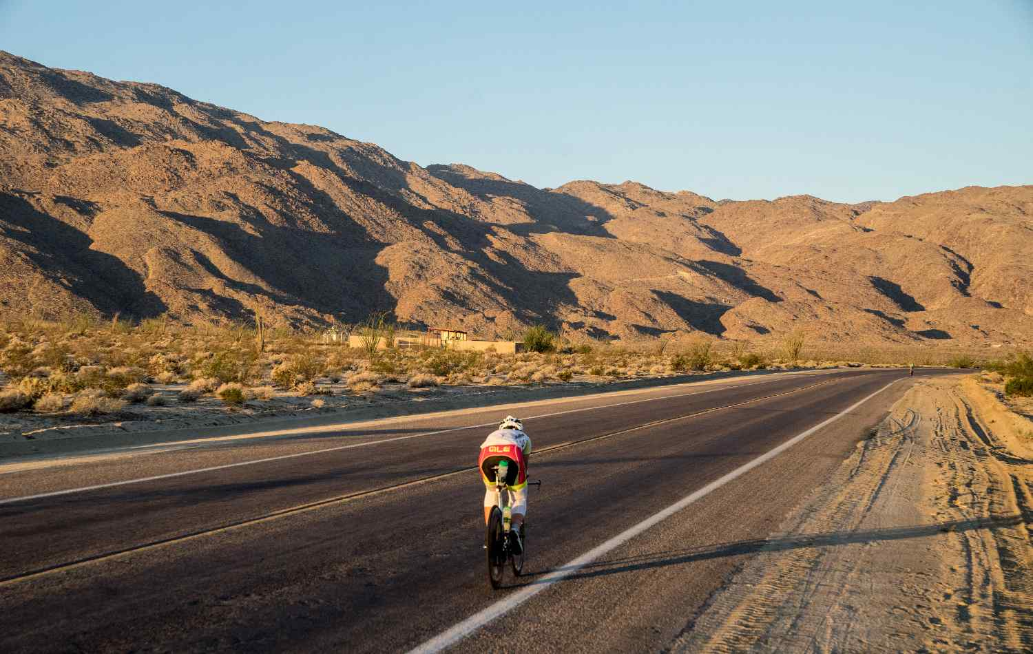 A person cycling on a road surrounded by mountains