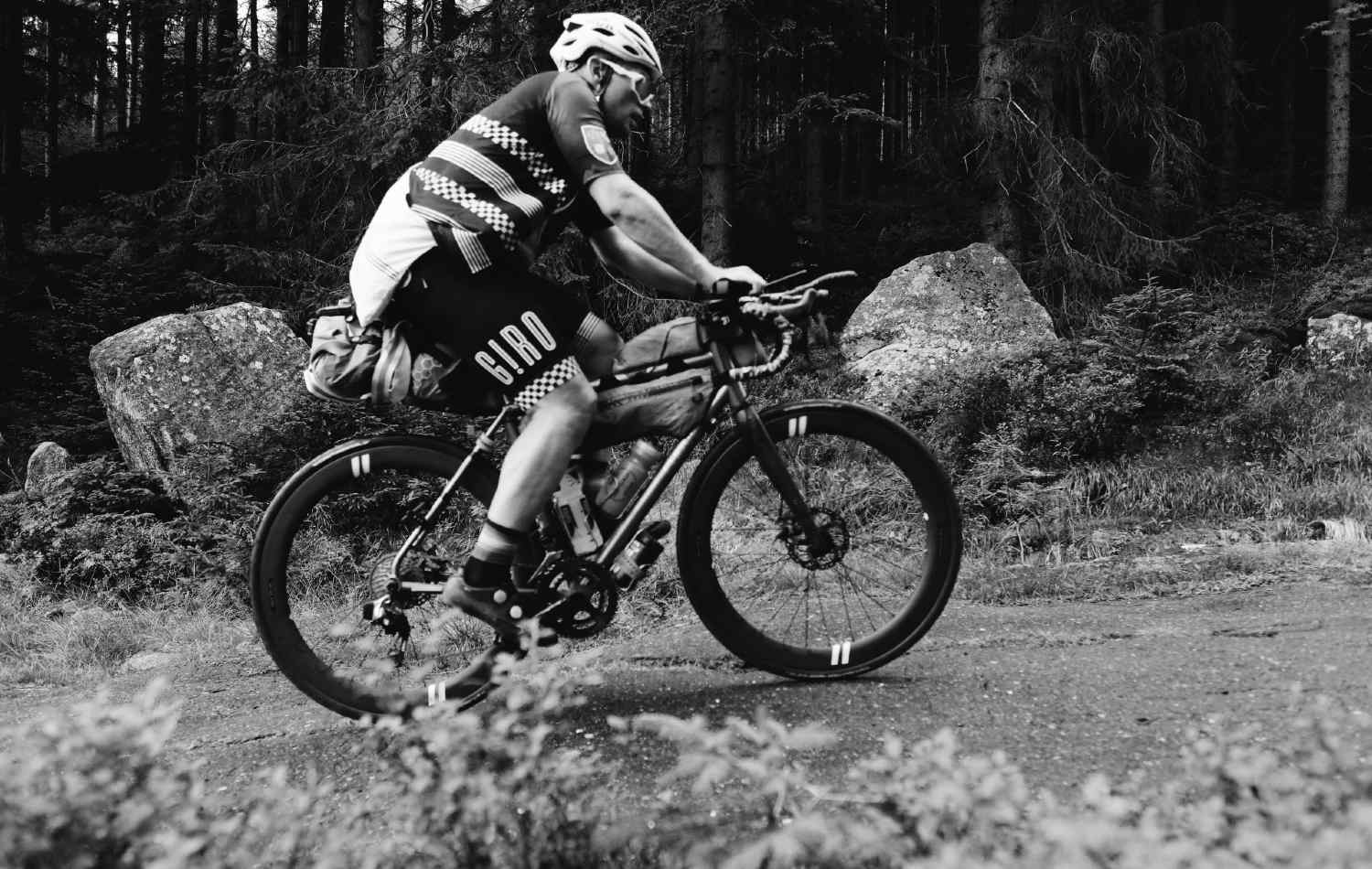Matt Falconer in black and white Riding a bike in a dirt road with a full bikepacking equipment