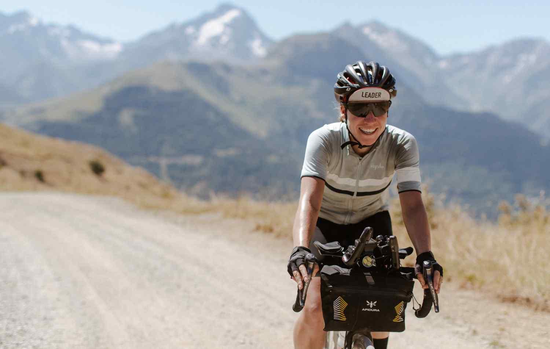 Fiona Kolbinger cycling in the mountain with handlebar bag on her bike