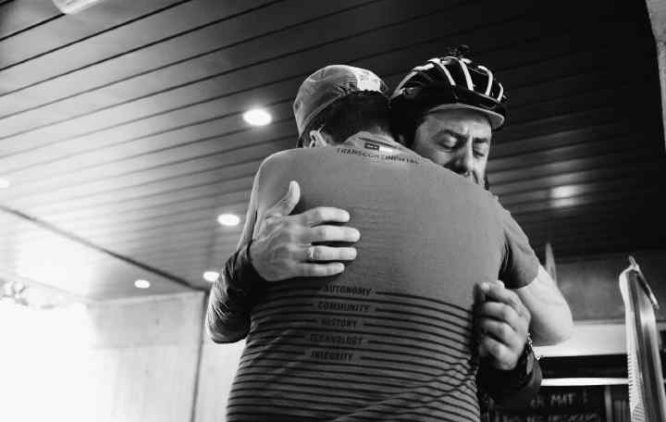 Two men in black and white hugging each other