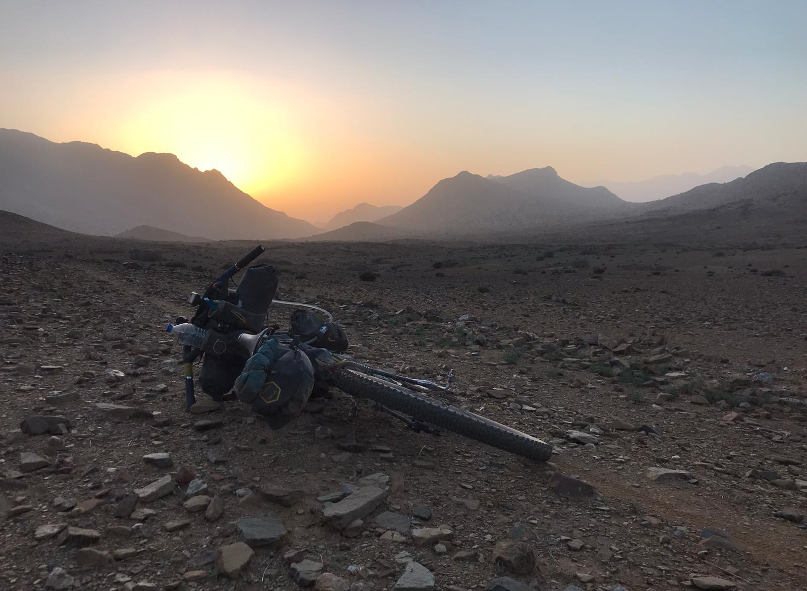 A bike with a full bikepacking equipment in the middle of a rocky dirt road