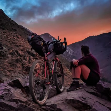 A woman sitting on the rocks of a mountain next to her bike with cycling bags on it watching the sunset