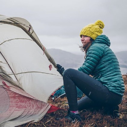 a woman preparing a tent in the middle of a mountain