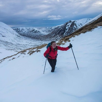 A woman hiking in a mountain full of snow