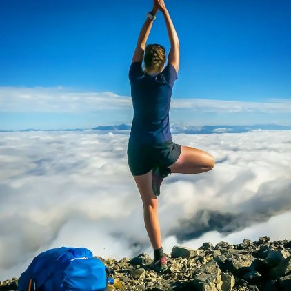 A woman practising yoga at the top of a mountain