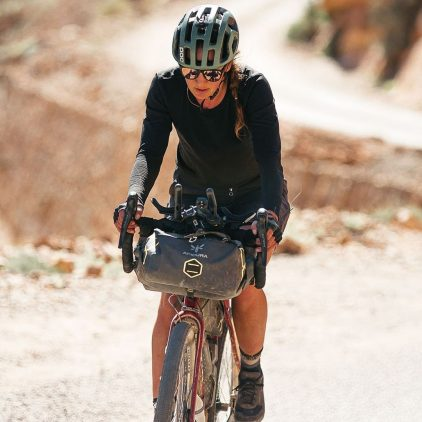A woman cycling in a gravel road with a handlebar bag on her bike