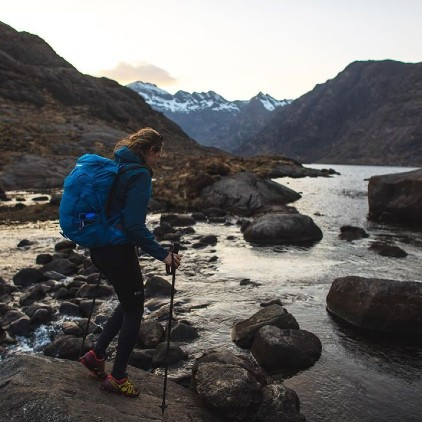 a woman crossing a small river with a full outdoor equipment