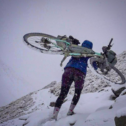 a woman carrying her bike with a full bikepacking kit on it above her shoulders through a snowy mountain