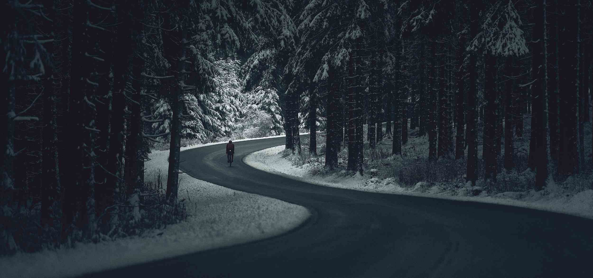 A road with a cyclist in the middle of a snowy forest in the night