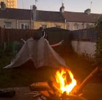 A woman camping on her backyard: a tent next to a wood fire