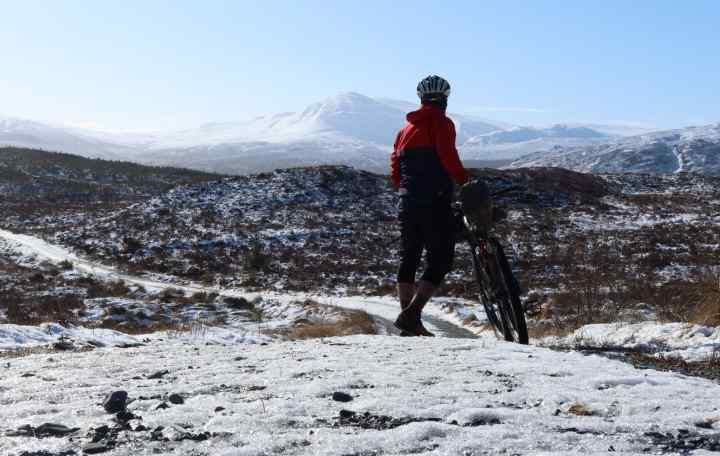 Markus standing next to his bike in a snowy dirt road in front of mountains